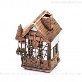 Mini Keramikhaus. Räucherhaus Nr. 2 mit Blumen auf Fensterbank.