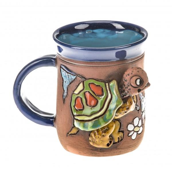 Blaue Keramiktasse mit Schildkröte, die einen Schmetterling fängt