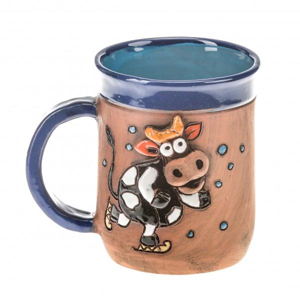 Blaue Keramiktasse mit einer rutschenden Kuh