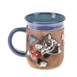 Blaue Keramiktasse mit einer Schmetterling fangenden Katze