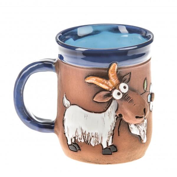 Blaue Keramiktasse mit einer weißen Ziege, die eine blaue Blume frisst.