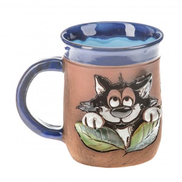 Blaue Keramiktasse mit einer Katze hinter einem Erdbeerenbusch