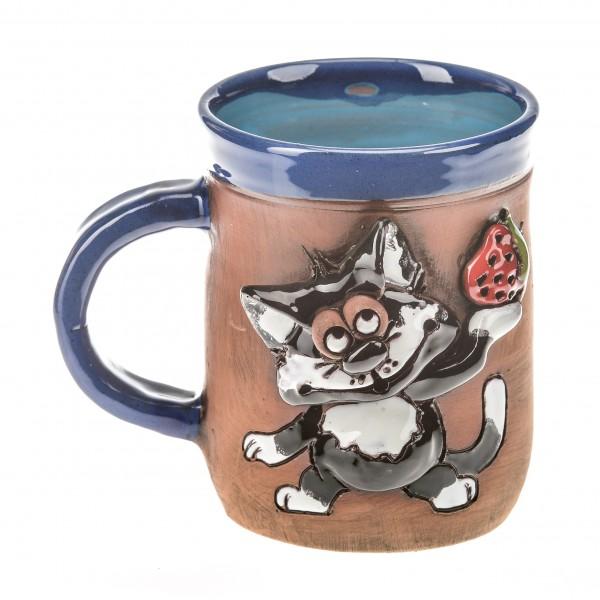Blaue Keramiktasse mit eine Erdbeere haltender Katze