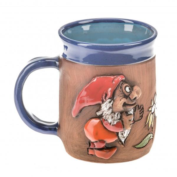 Blaue Keramiktasse mit einem roten Schlumpf und einer Blume