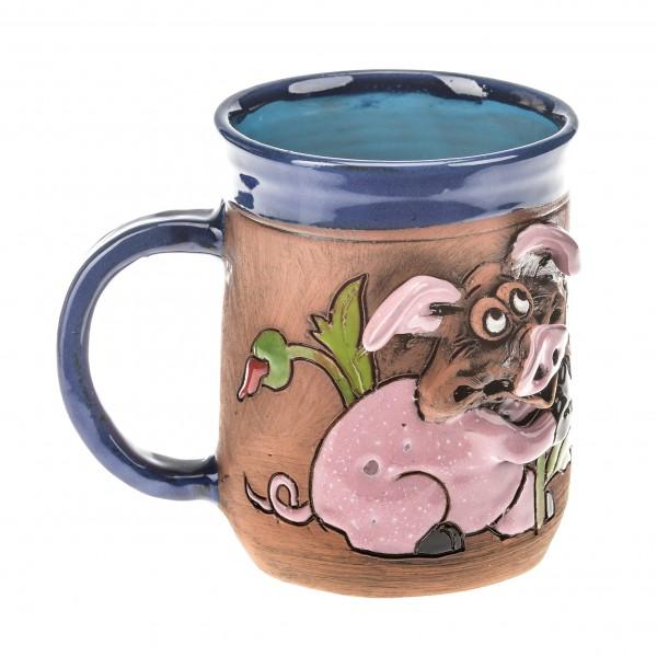 Blaue Keramiktasse mit einen Mohn haltendem Schwein