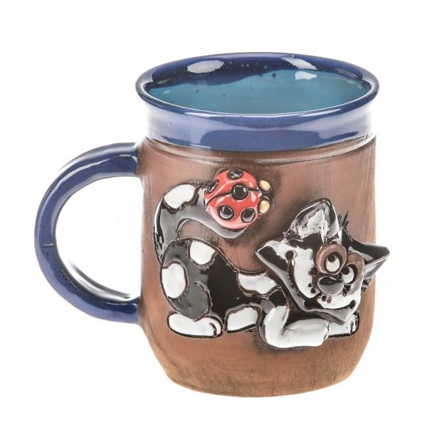 Blaue Keramiktasse mit einer Katze mit Marienkäfig auf ihrem Schwanz